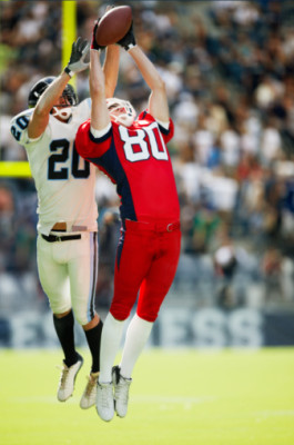 Professional football receiver and defended leaping for catch in crowded stadium